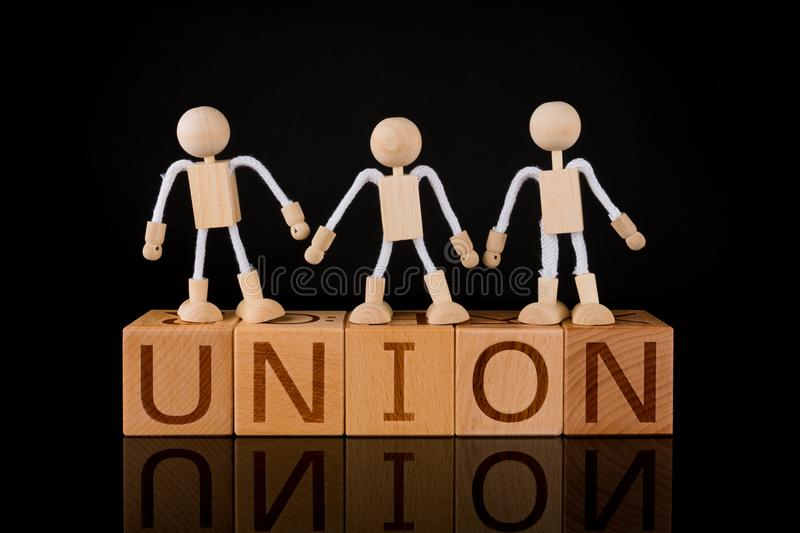 "Teamwork concept, Stick Figuers Standing on Wood cube block with word ""UNION"". royalty free stock photography"