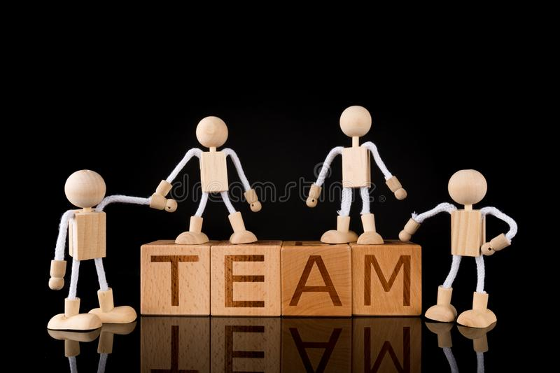 """Teamwork concept, Wood cube block with word """"TEAM"""" and Wooden Stick Figures team. Black background, reflecting stock photo"""