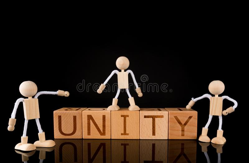 "Teamwork concept, Wood cube block with word ""UNITY"" and Wooden Stick Figures team. royalty free stock image"