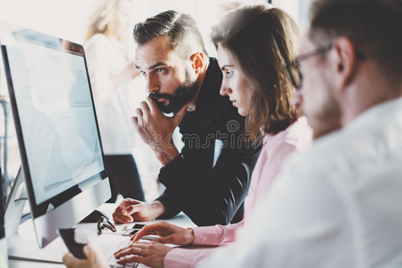 Teamwork concept.Young creative coworkers working with new startup project in modern office.Group of three people stock photo