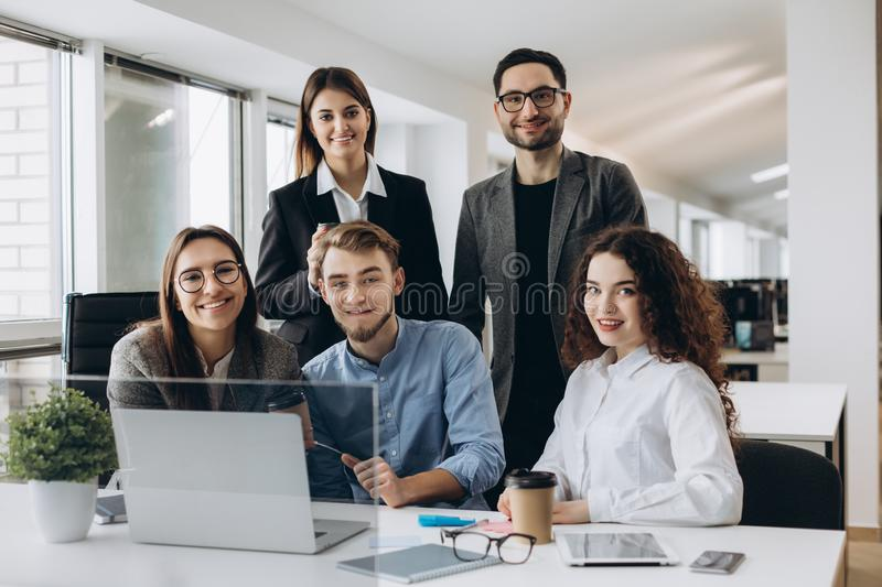 Teamwork concept.Young creative coworkers working with new startup project in modern office and looking at camera royalty free stock photo