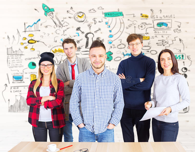 Teamwork concept. Young team of attractive european men and women standing at workplace with creative business sketch. Teamwork concept stock image