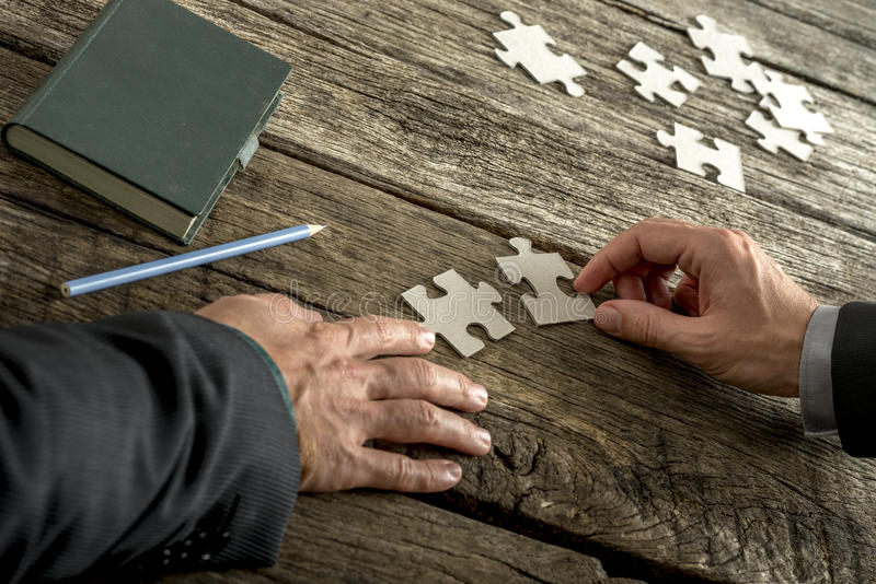 Teamwork and cooperation between two business people as they join forces to combine matching puzzle pieces royalty free stock photo