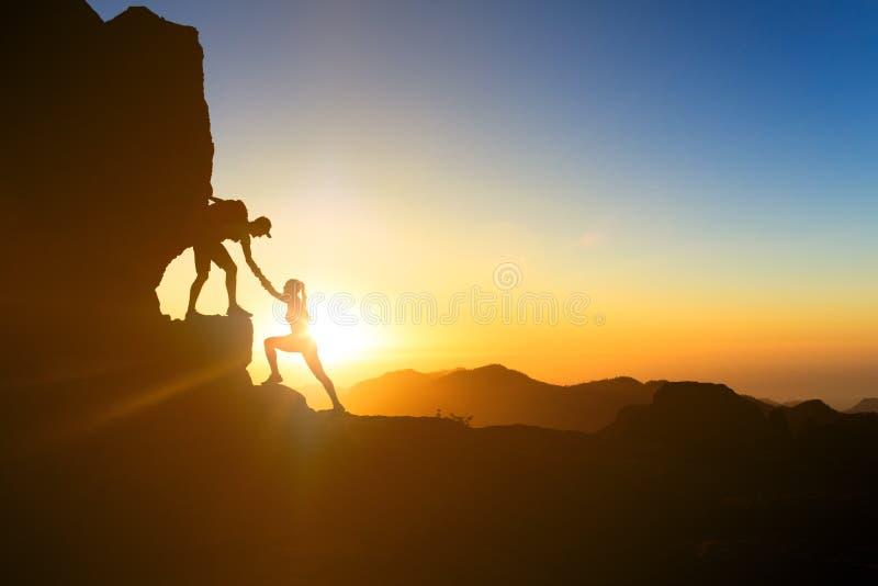 Teamwork couple climbing helping hand. Teamwork couple helping hand trust help silhouette in mountains, sunset. Team of climbers man and woman hikers, help each stock photo