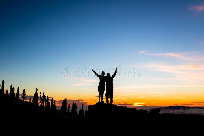 Teamwork couple climbing and reaching mountain peak. Silhouette of celebrating climbers team over mountains sunset. Man and women hikers looking at stock photography