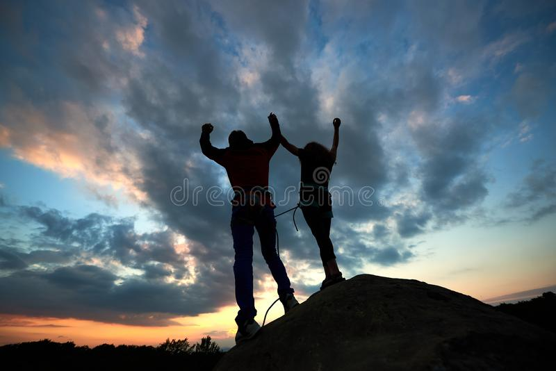 Silhouettes of man and woman on top of mountain. Hikers couple with raised arms on dramatic sky at sunset background. Teamwork couple helping hand trust help royalty free stock image