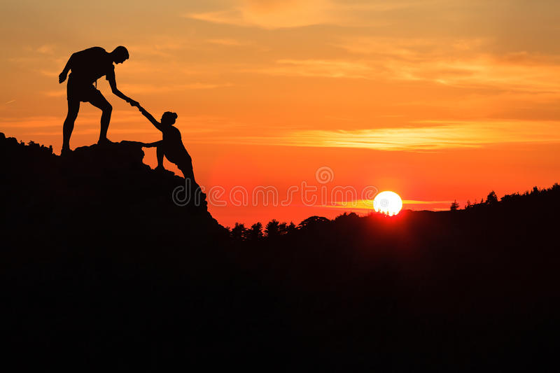 Teamwork couple helping hand trust in inspiring mountains. Teamwork couple helping hand trust silhouette in inspiring mountains. Team of climbers assistance men