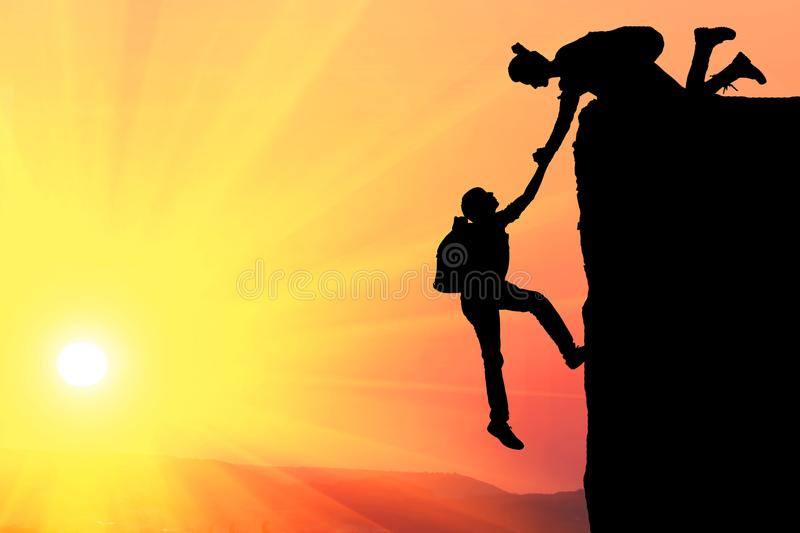 Teamwork couple hiking help each other trust assistance silhouette in mountains, sunset. Teamwork of man and woman hiker helping e. Ach other on top of mountain stock photos