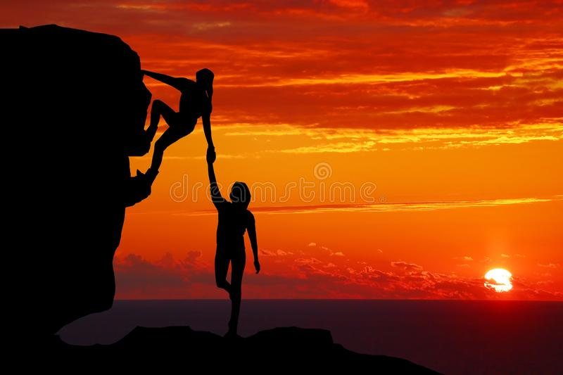 Teamwork couple hiking help each other trust assistance silhouette in mountains, sunset. Teamwork of man and woman hiker helping e. Ach other on top of mountain royalty free stock photos