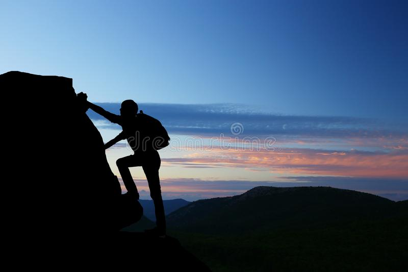Teamwork couple hiking help each other trust assistance silhouette in mountains, sunset. Teamwork of man and woman hiker helping e. Ach other on top of mountain stock photography