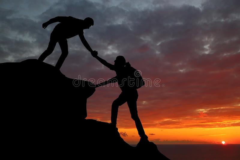 Teamwork couple hiking help each other trust assistance silhouette in mountains, sunset. Teamwork of man and woman hiker helping e. Ach other on top of mountain royalty free stock photo