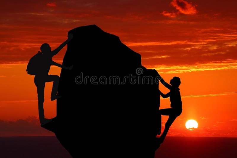 Teamwork couple hiking help each other trust assistance silhouette in mountains, sunset. Teamwork of man and woman hiker helping e. Ach other on top of mountain stock photo