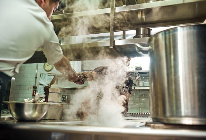 teamwork Cozinheiro chefe do restaurante que dá um moedor de pimenta a seu assistente quando processo de cozimento na cozinha fotos de stock royalty free