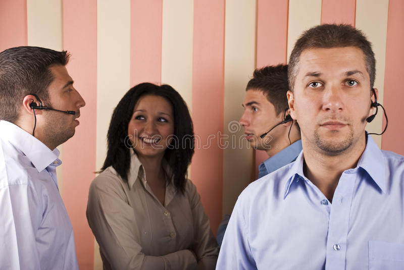 Teamwork customer service. With a mid adult man in front and others that having a conversation in background.Check also,for pictures similar or the same series stock photography