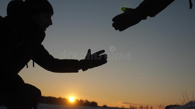 Teamwork desire to win. close-up. Climbers help friend climb stretch of helping hand. Silhouette of travelers in winter royalty free stock image