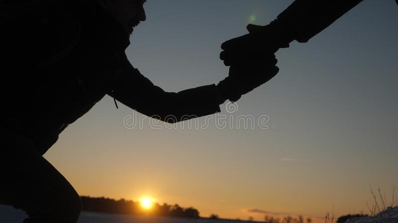 Teamwork desire to win. close-up. Climbers help friend climb stretch of helping hand. Silhouette of travelers in winter royalty free stock images
