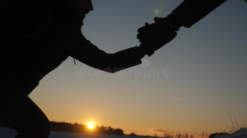 Teamwork desire to win. close-up. Climbers help friend climb stretch of helping hand. Silhouette of travelers in winter stock photography