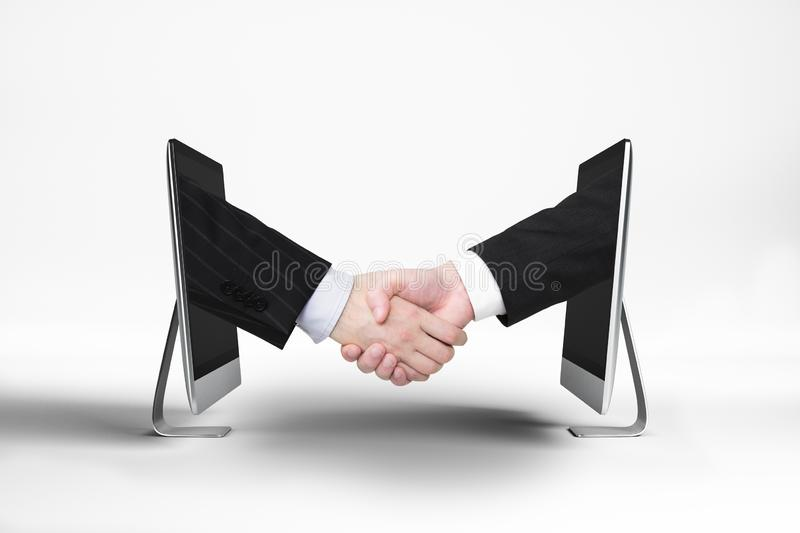 Teamwork and digital business concept. Businessmen shaking hands through computer screens on white background with shadow. Teamwork and digital business concept royalty free stock photos
