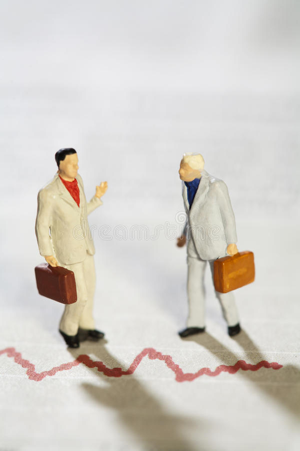 Teamwork And Discussion. Two miniature model businessmen having a deep discussion above a red line graph royalty free stock image