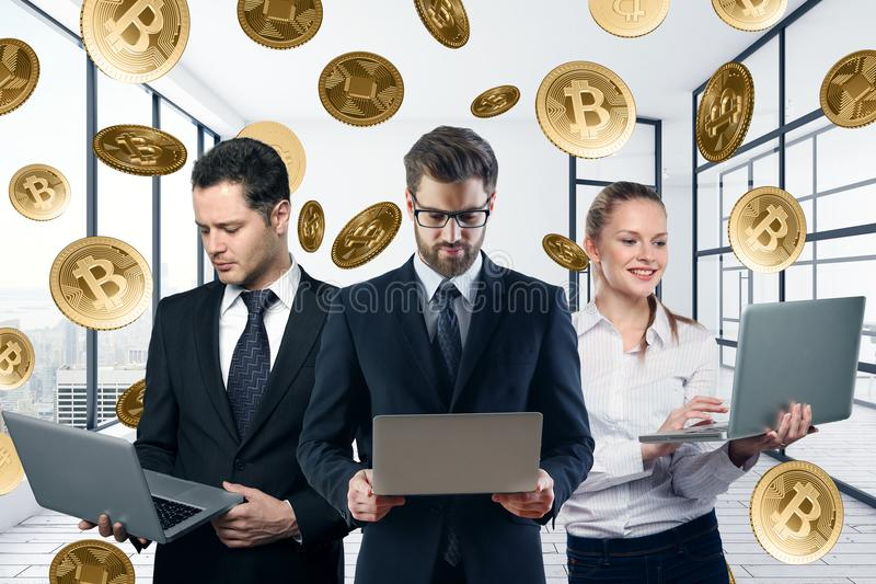 Teamwork and e-commerce concept. Businessmen and women using laptops in abstract office interior with bitcoin rain. Teamwork and e-commerce concept stock photo