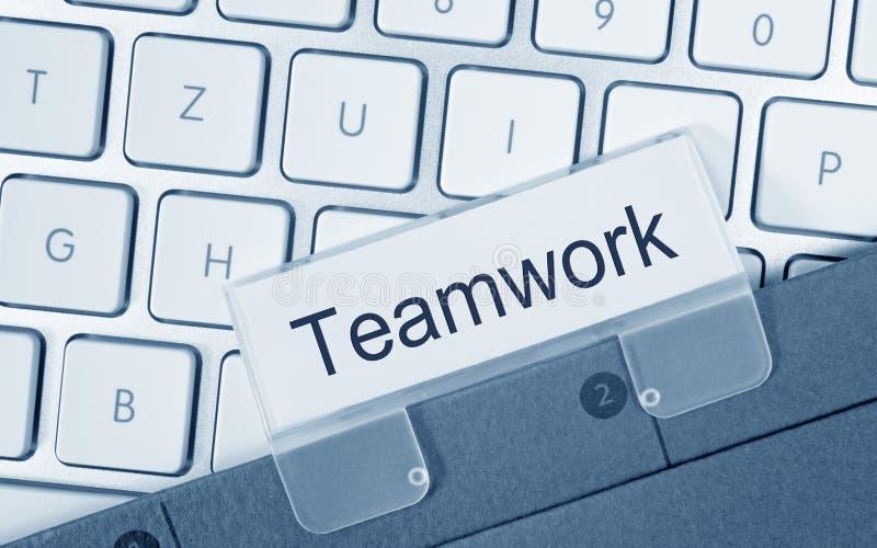 Teamwork - folder on computer keyboard stock photography