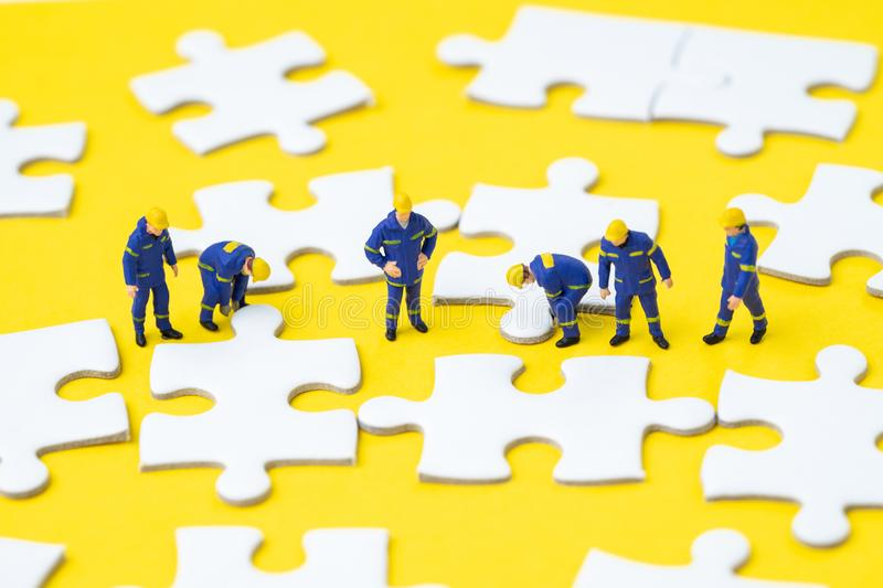 Teamwork help solving problem and solution metaphor concept, min. Iature people worker, staffs or employee help finishing jigsaw puzzle pieces on yellow royalty free stock photo