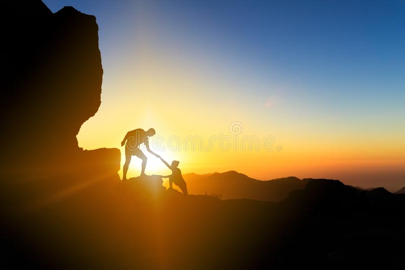 Teamwork helping hand couple climbing at sunset. Teamwork couple helping hand trust help silhouette in mountains, sunset. Team of climbers man and woman hikers stock photo