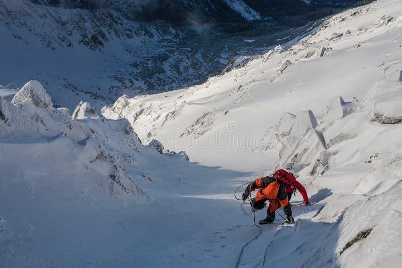 Teamwork i alpinism bergsbestigning Travers av berget royaltyfri bild