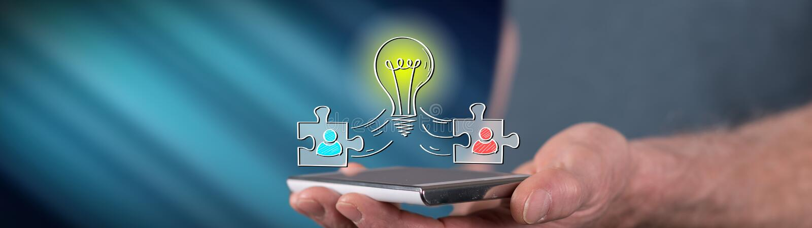 Concept of teamwork idea. Teamwork idea concept above a smartphone held by a man royalty free stock photography