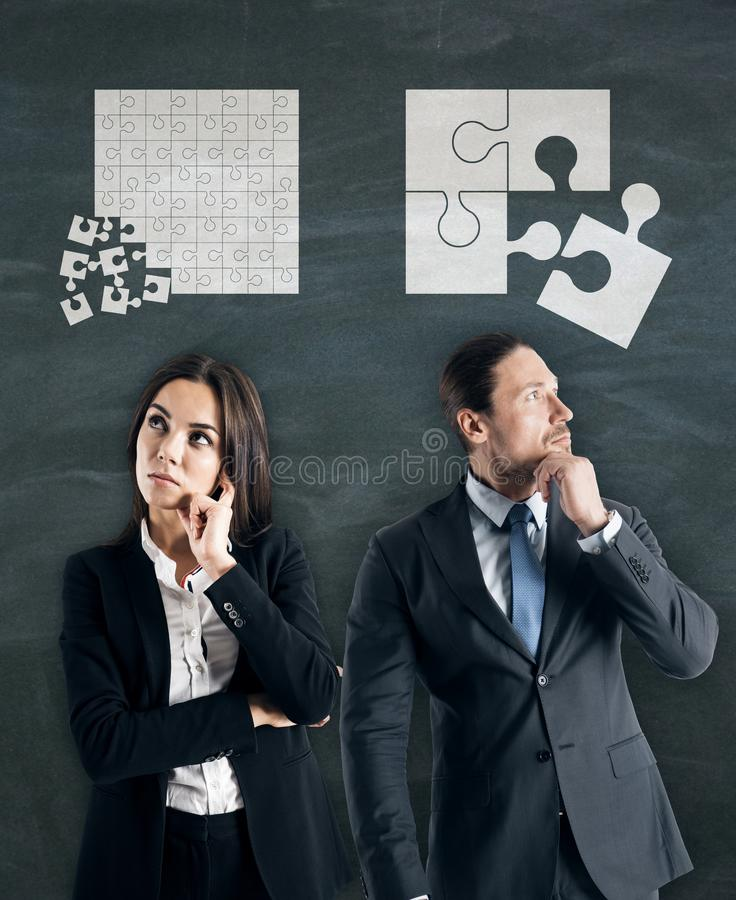 Teamwork and idea concept. Attractive young european businessman and women with puzzles overhead on chalkboard background. Teamwork and idea concept royalty free stock photos