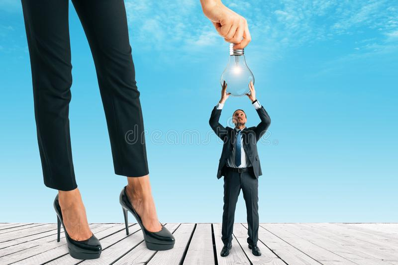 Teamwork and idea concept. Businesswoman hanging lamp to tiny businessman on blue sky background. Teamwork and idea concept stock photos