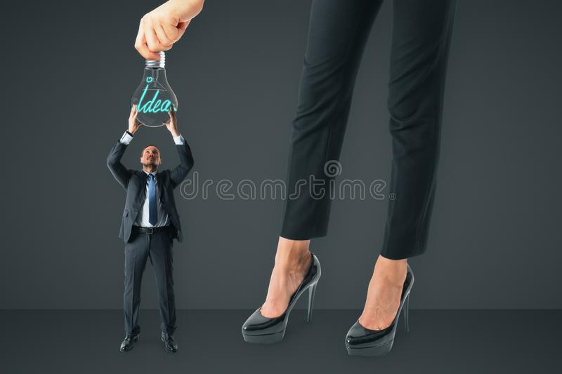 Teamwork and idea concept. Businesswoman hanging lamp to tiny businessman on gray background. Teamwork and idea concept stock photo