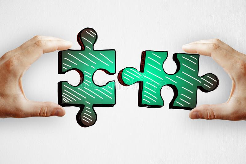 Teamwork and idea concept. Hands holding drawn green puzzle pieces on subtle paper background. Teamwork and idea concept royalty free stock image