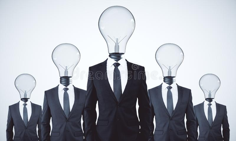 Teamwork and idea concept. Lamp headed businesspeople standing on white background. Teamwork and idea concept stock image