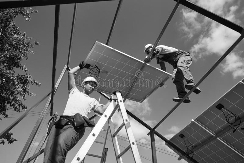 Teamwork for installing innovative solar pannels on the roof. royalty free stock photos