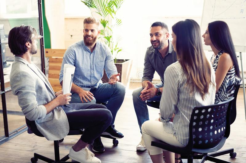 Teamwork is a key to success. Business people in smart casual wear talking and smiling while having a brainstorm meeting. In office royalty free stock photo