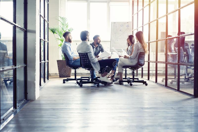 Teamwork is a key to success. Business people in smart casual wear talking and smiling while having a brainstorm meeting royalty free stock image