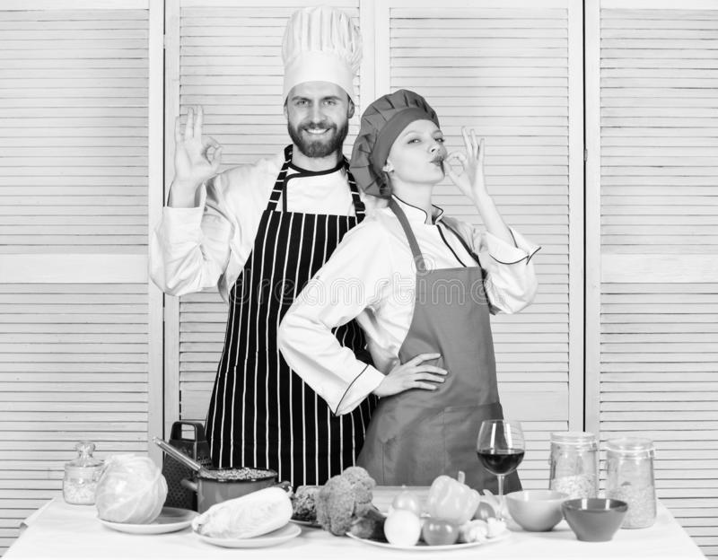 Teamwork in kitchen. Couple cooking dinner. Woman and bearded man culinary partners. Delicious family dinner. Reasons stock image