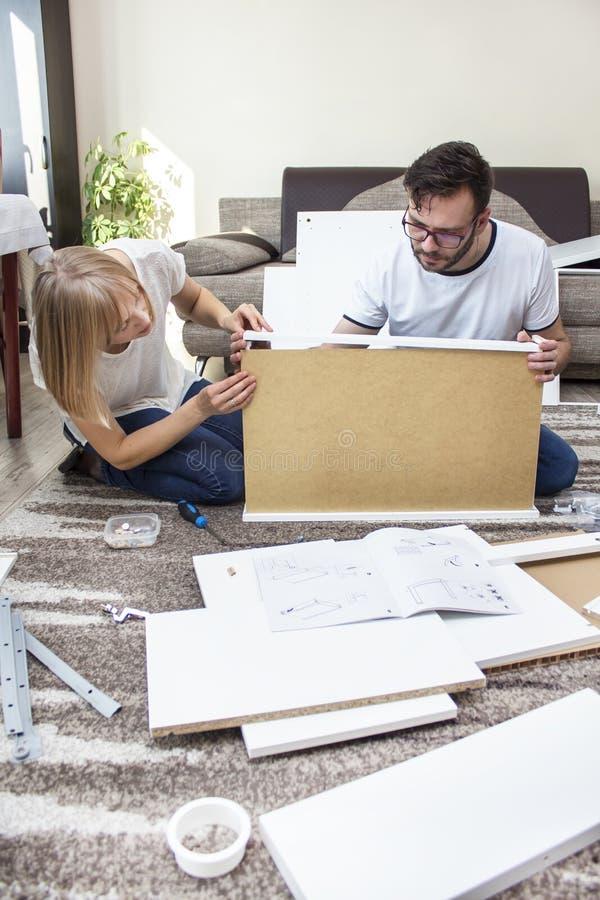teamwork La torsione della moglie e del marito insieme la mobilia nel salone, abbinante gli elementi di legno dell'insieme della  immagine stock libera da diritti