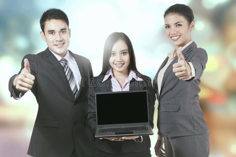 Teamwork with laptop and blurred light. Group of businesspeople with laptop showing thumbs up, shot with blurred light background royalty free stock photos