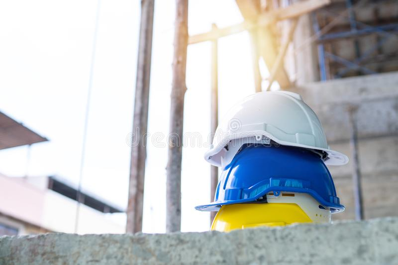 Teamwork and leadership concept, safety white, blue and yellow helmet in construction site for safe engineer and construction stock image