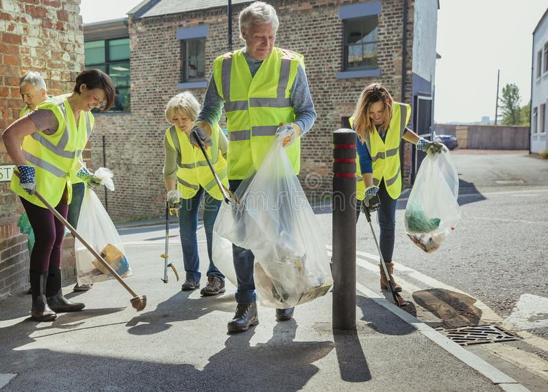 Teamwork Makes the Dreamwork. A group of five people wearing high visibility jackets participating in a city clean-up together stock photos