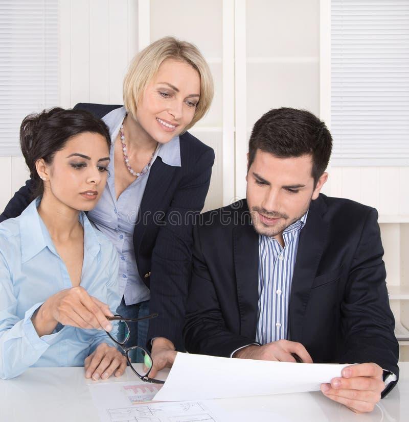 Teamwork mellan tre affärspersoner på skrivbordet på kontoret. arkivfoton