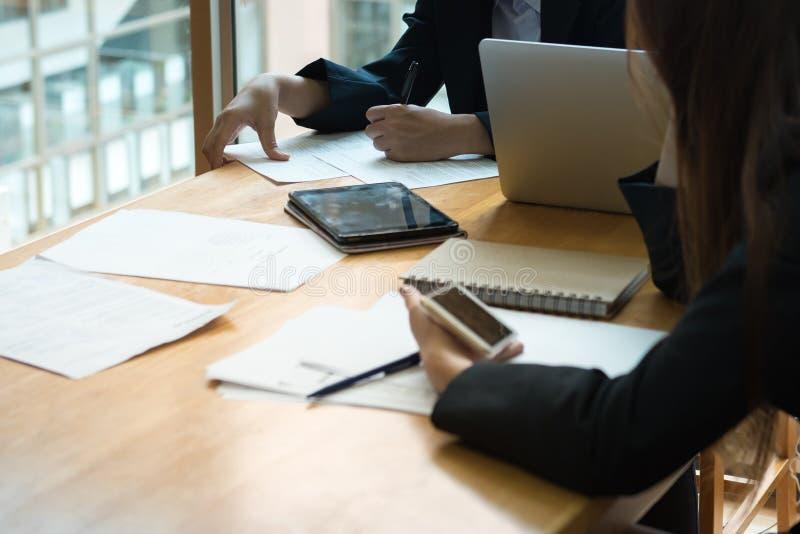 teamwork mulheres de negócios novas que sentam-se no olhar da tabela em de papel e imagem de stock