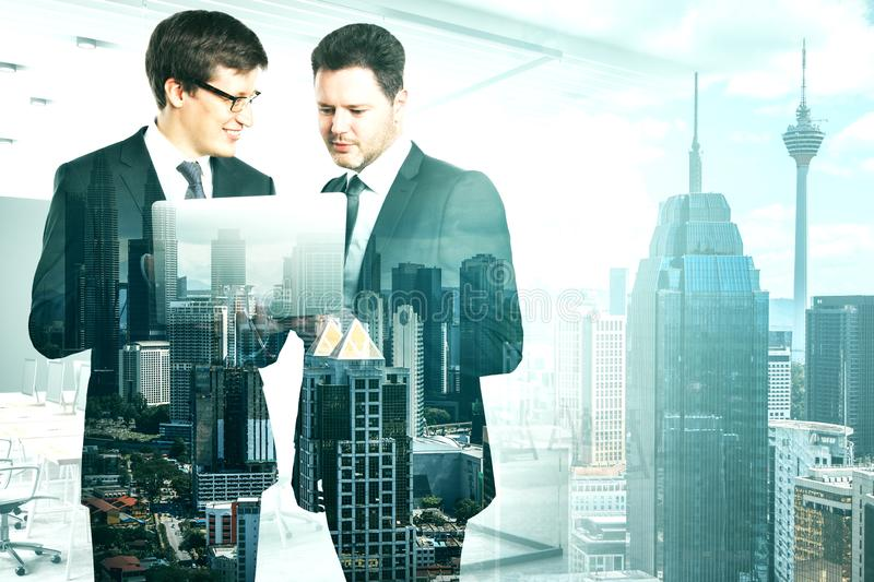 Teamwork and network concept. Attractive young european businessmen using laptop together on blurry office New York city interior background. Teamwork and stock illustration
