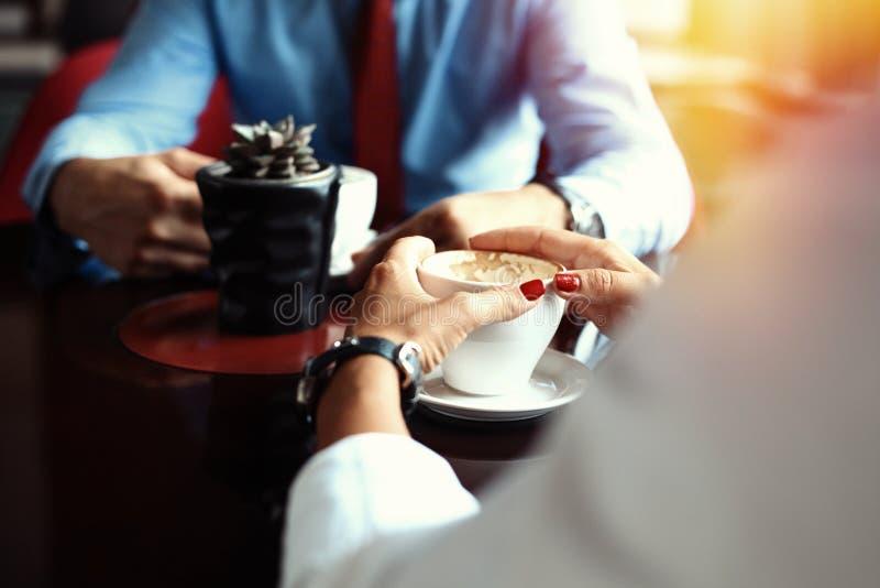teamwork O homem de negócios e a mulher de negócios que sentam-se na tabela na cafetaria e discutem o plano de negócios Na tabela foto de stock