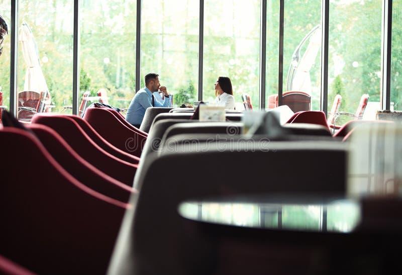 teamwork O homem de negócios e a mulher de negócios que sentam-se na tabela na cafetaria e discutem o plano de negócios Na tabela imagens de stock royalty free
