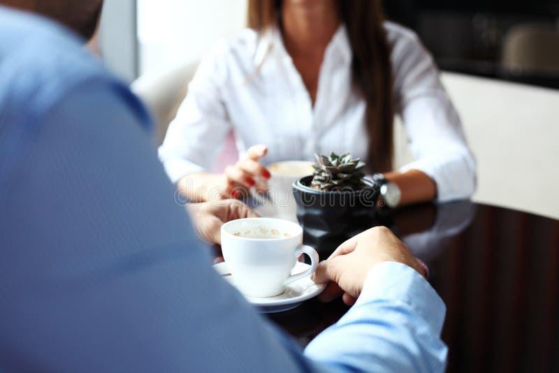 teamwork O homem de negócios e a mulher de negócios que sentam-se na tabela na cafetaria e discutem o plano de negócios Na tabela imagens de stock