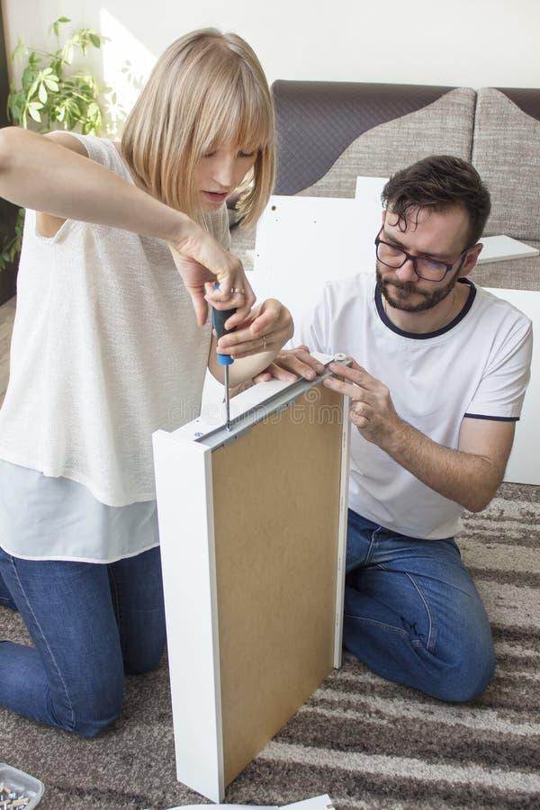teamwork O marido e a esposa estão girando a mobília junto na sala de visitas imagens de stock