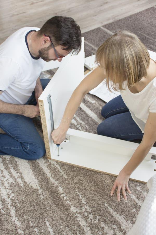 teamwork O marido e a esposa estão girando a mobília junto na sala de visitas fotografia de stock